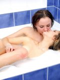 Cute teens play in the bathtub together both with small boobies wet with bubbles