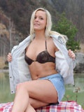 Sassy pulls up her denim skirt and fingers her pussy outdoors